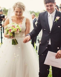 after the wedding ceremony the couple walked down the aisle with guests throwing rose petals